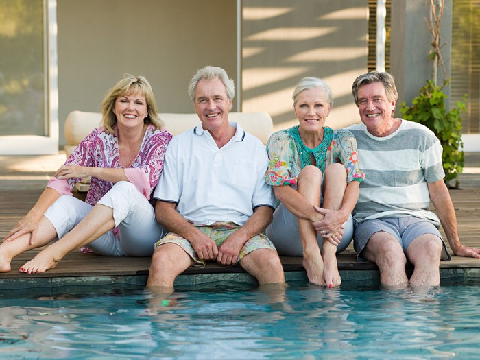 Four 70-something people sitting with their feet dangling in the pool.