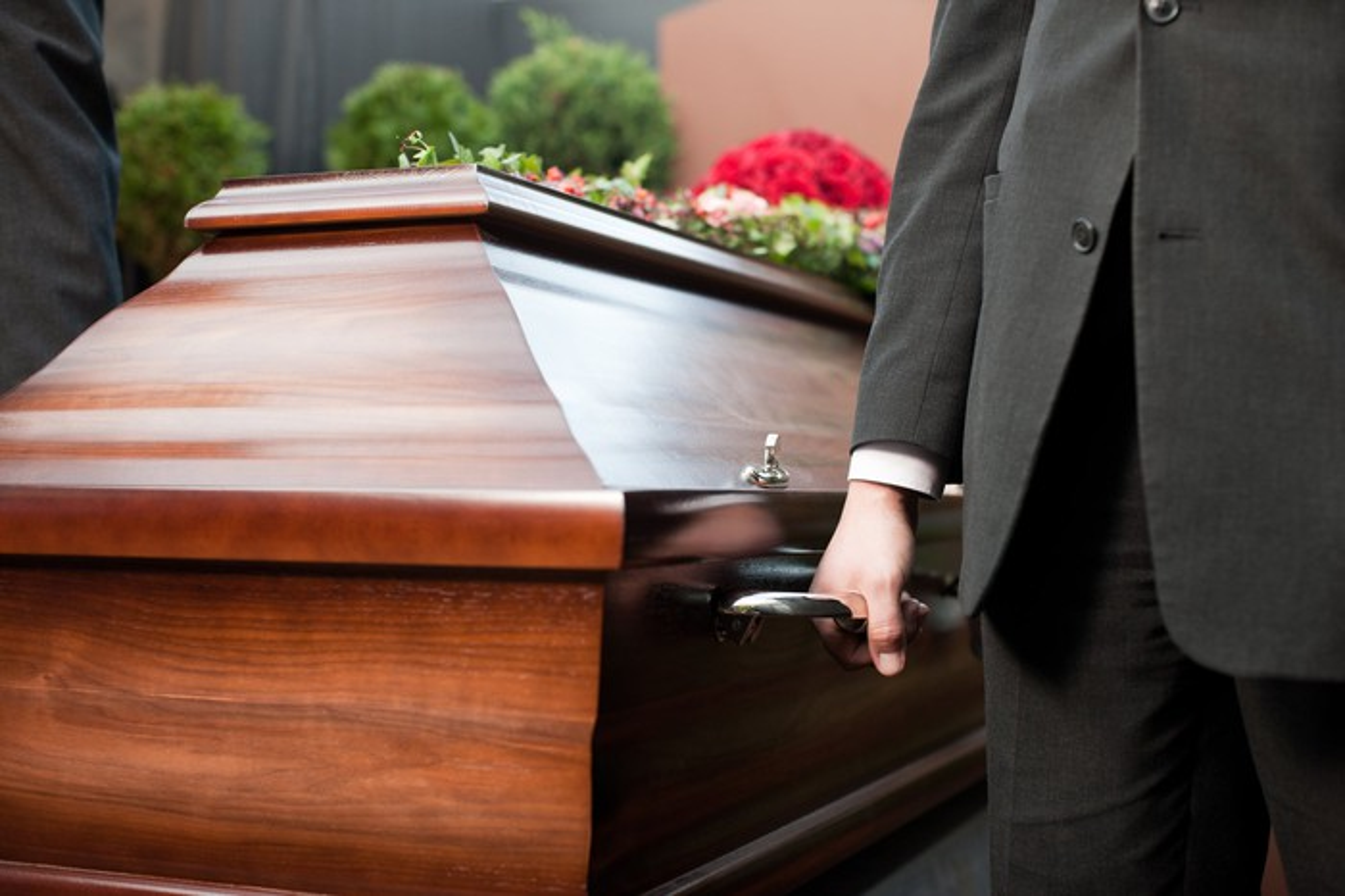 Pallbearer holding onto a wooden casket