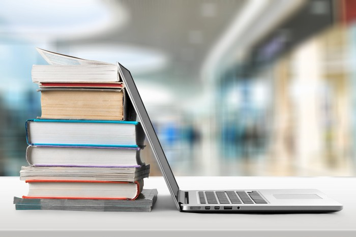 The lid of an open laptop leans against a stack of textbooks.
