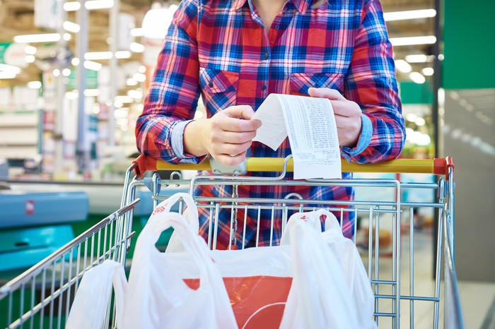Person in grocery store standing behind cart filled with bags, looking at a receipt