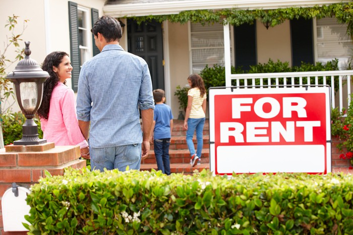 Family of four standing outside house with a For Rent sign