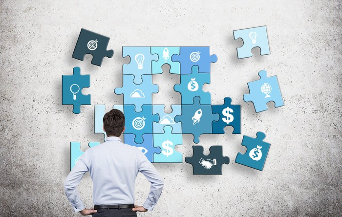 man with hands on hips looking at a puzzle of different business components on a concrete wall