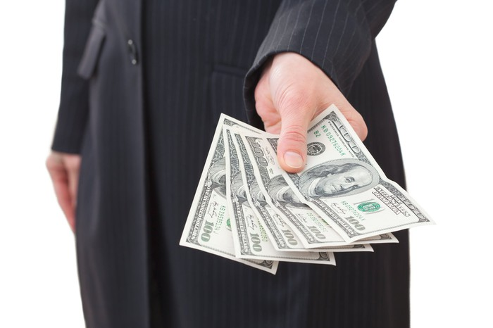 torso seen of man in suit, holding out hundred dollar bills