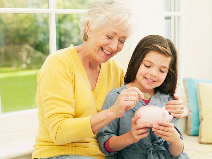Grandmother hugging grandchild and putting coins into her piggy bank.