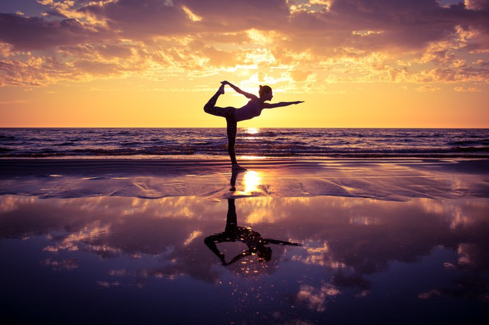 Woman doing yoga on beach in the early morning.