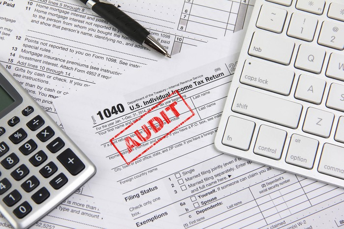 "A 1040 stamped in red: ""AUDIT"" and other tax documents spread out on a desk with a calculator"