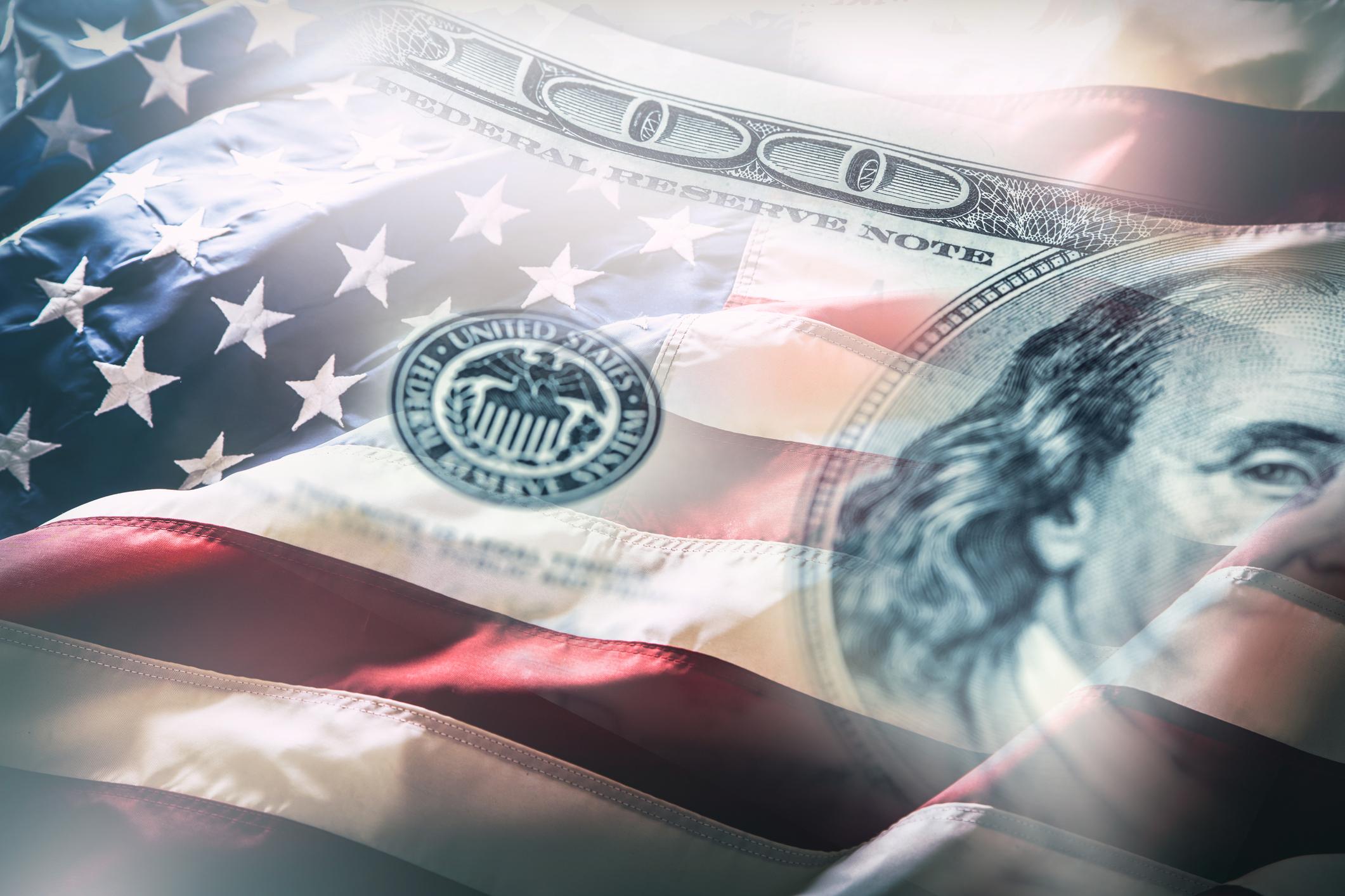 Semi-transparent hundred dollar bill superimposed on an American flag