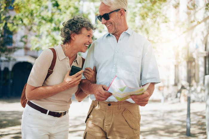Retired couple laughing while walking around town