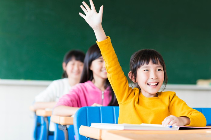 A child raises her hand while learning in school.