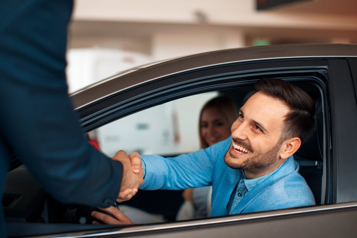 A young, smiling man shaking hands with a car salesman while still inside a car he's buying with his wife.