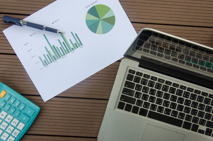 A paper with a bar chart and pie chart next to a laptop