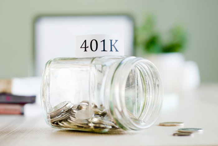 """A glass jar partially filled with quarters is labeled """"401K."""""""