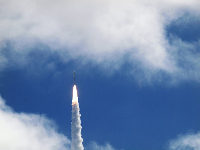 A rocket launch in a blue sky with clouds.