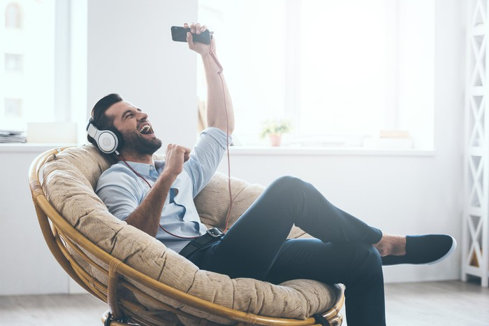 Young man sitting in papasan chair, wearing headphones and listening to music on smartphone
