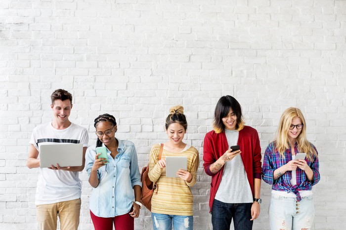 Five young people lined up against a white brick wall while looking at their smartphones, tablets, and laptops.