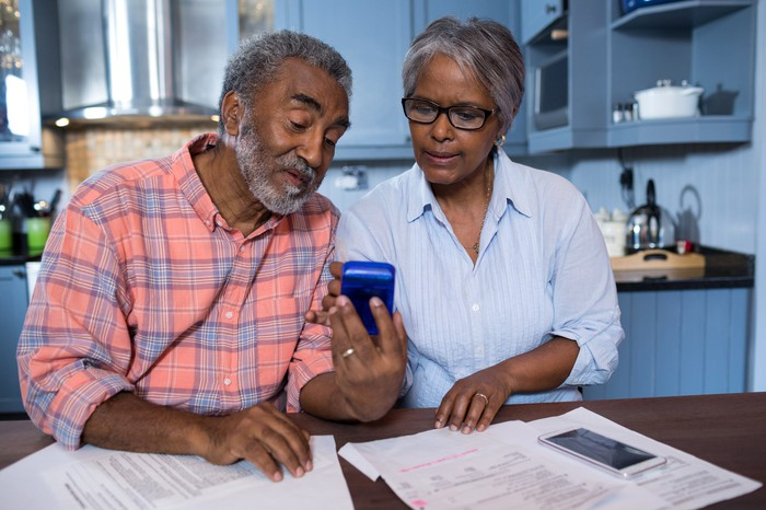 A mature African American couple consults a calculator while planning finances