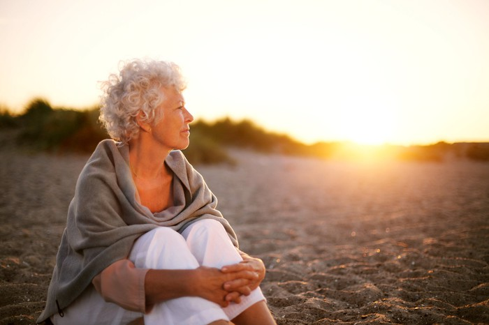A retired woman sits on a beach and gazes thoughtfully at the sunset.