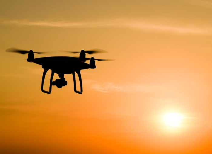 Silhouette of a drone with sun setting in the background