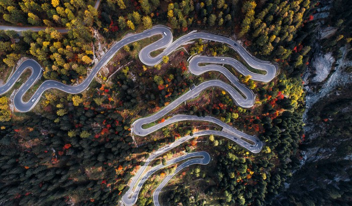 Drone footage of a road winding through a forest