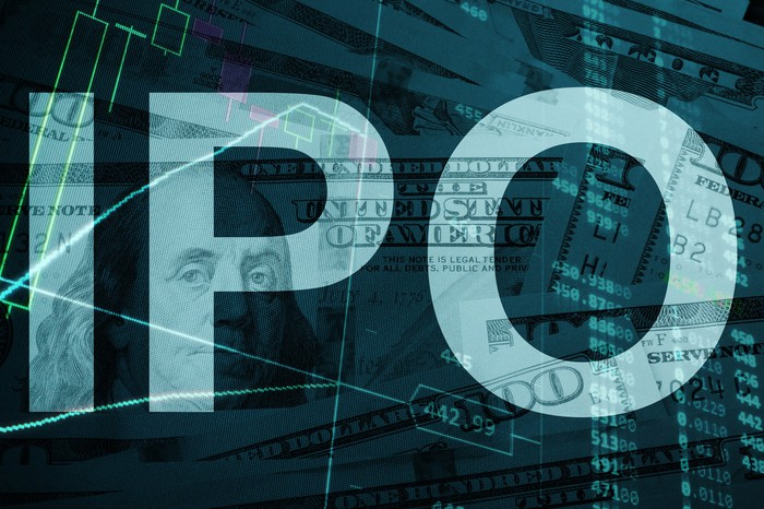 "The letters ""IPO"" superimposed over images of cash and a stock ticker board."