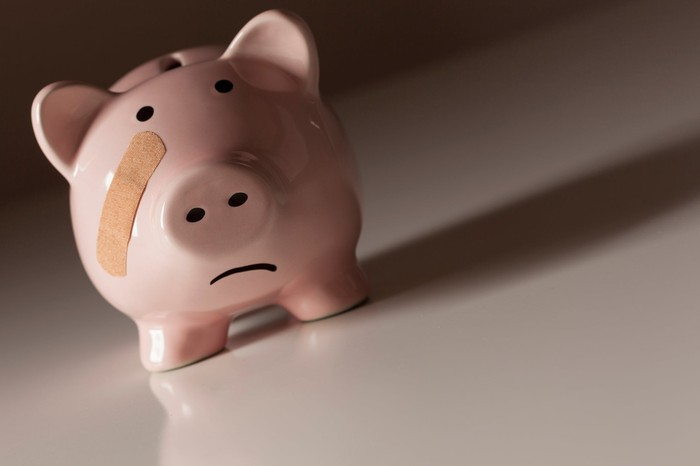 Piggy bank with a frown and bandage across his cheek.