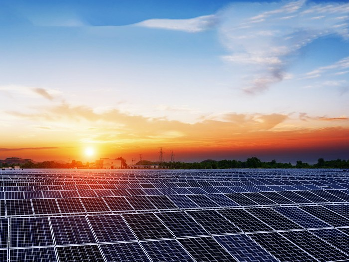 Array of solar panels with sun setting in the background