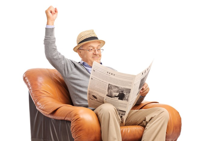 A smiling senior man sits in a chair with his fist raised in victory as he reads the newspaper.
