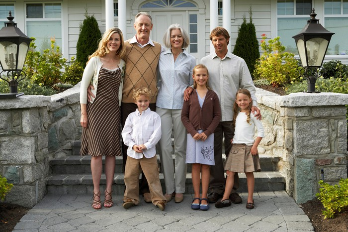 Three generations of a white, middle-class family stand in front of their home