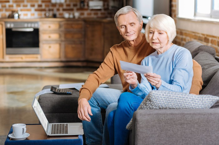 A retired couple sitting on a couch examine their mail.