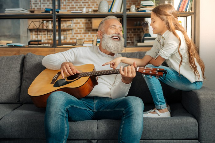 Grandfather chatting with granddaughter while holding a guitar.