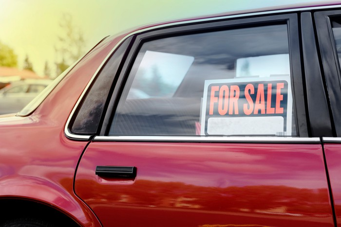 "A red car with a ""for sale"" sign in its rear passenger window."