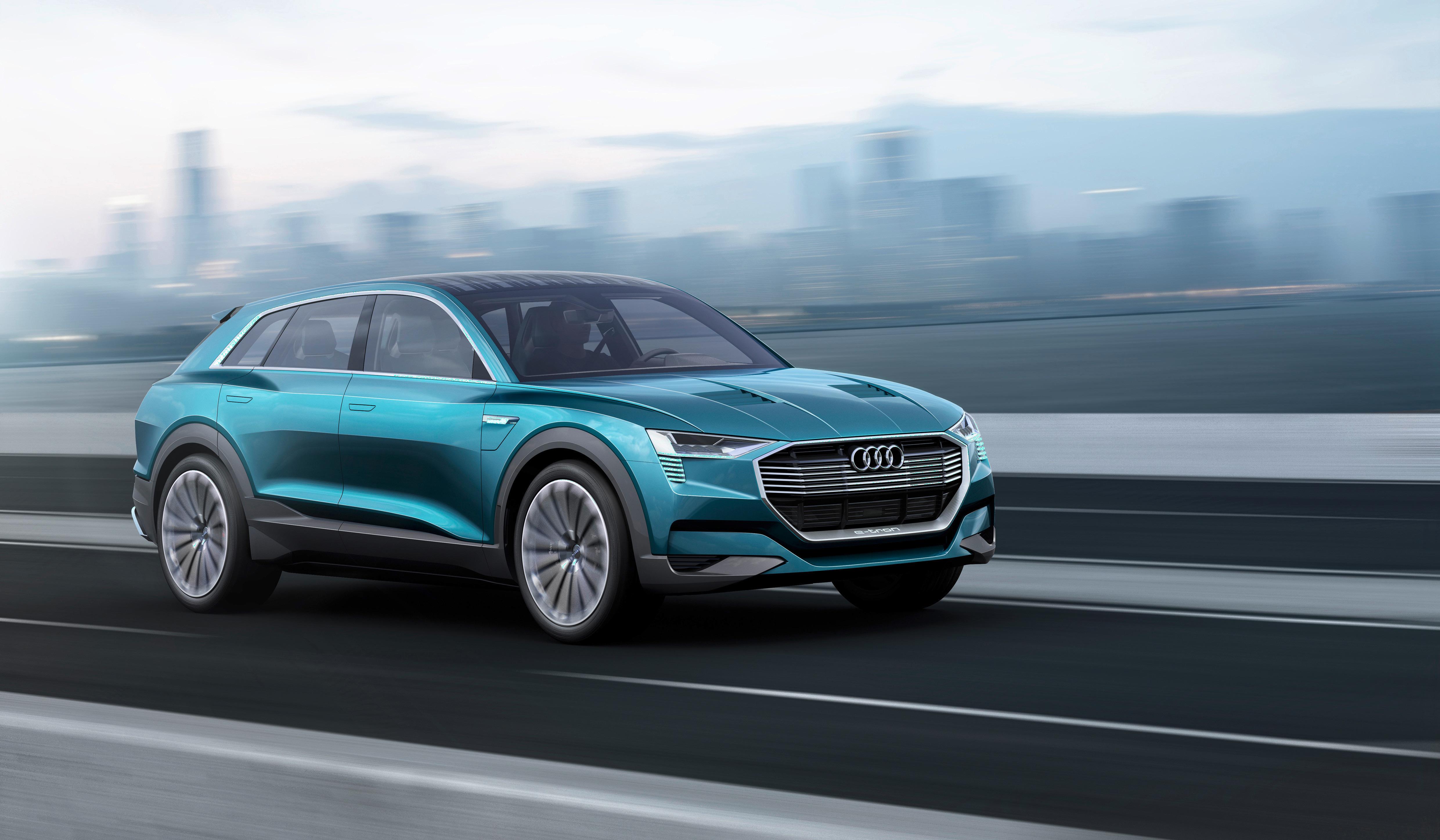 Audi's e-tron quattro concept SUV is shown on a desert landscape.
