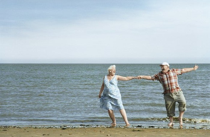 A senior man and woman dance happily on a beach in summer.