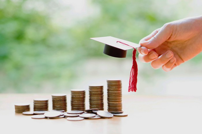 Stacks of coins with a hand placing a miniature mortarboard on the tallest one