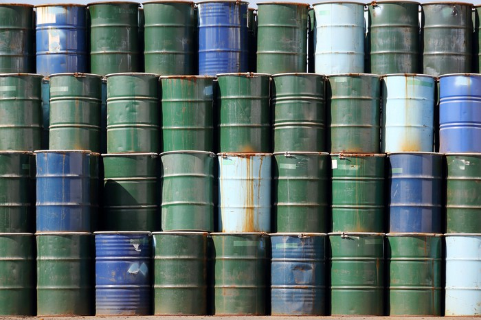 Four layers of green and blue oil barrels stacked up.