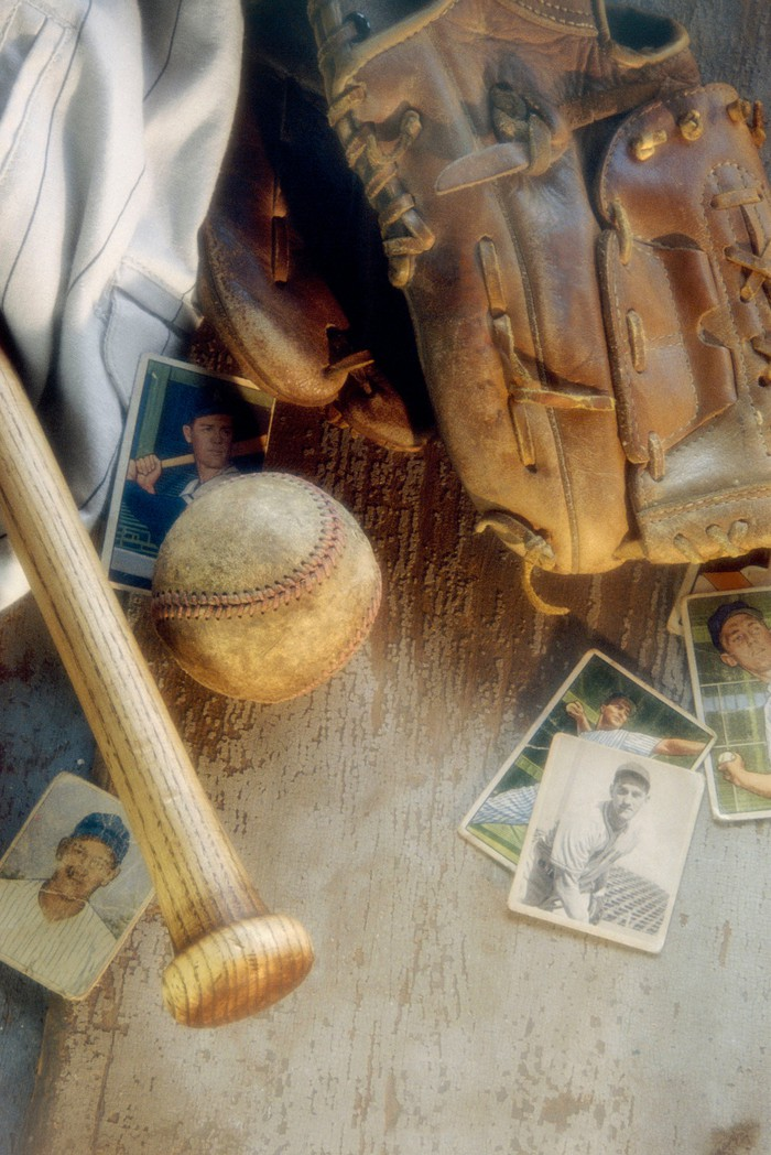 Old baseball cards with a bat, ball, and glove.