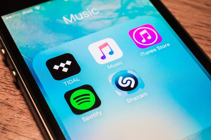 An image of an iPhone screen featuring several prominent streaming music apps including Spotify, Pandora, Apple Music, and more.