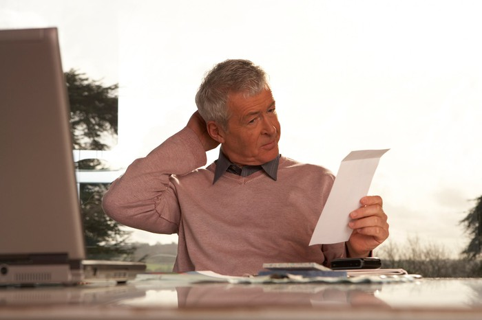 A retiree sits at a desk, scratching his head while looking at a piece of paper.