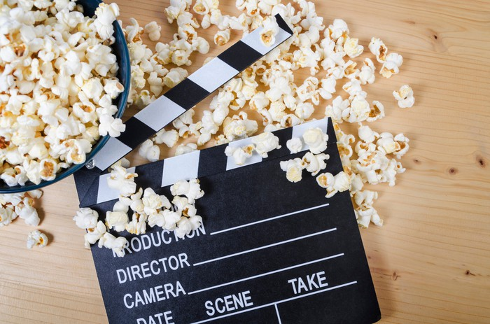 Movie clapper on wooden table with popcorn scattered around it