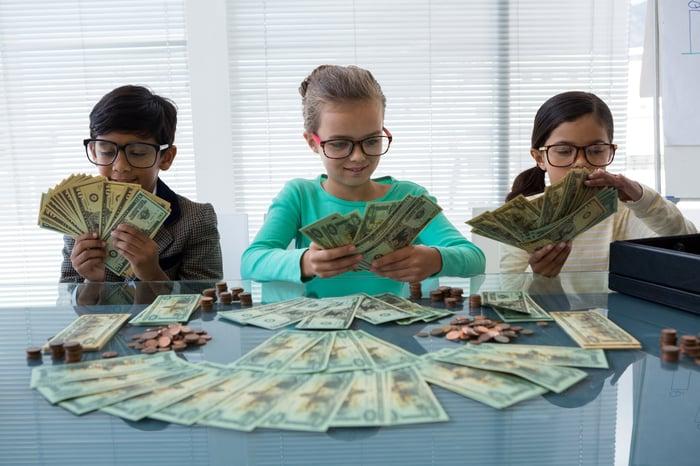 Three children counting money.