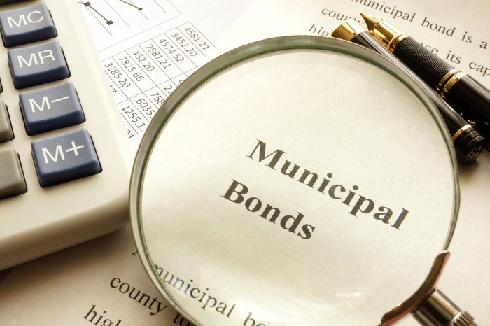 The words municipal bonds through a magnifying glass that's sitting next to a calculator and a pen.