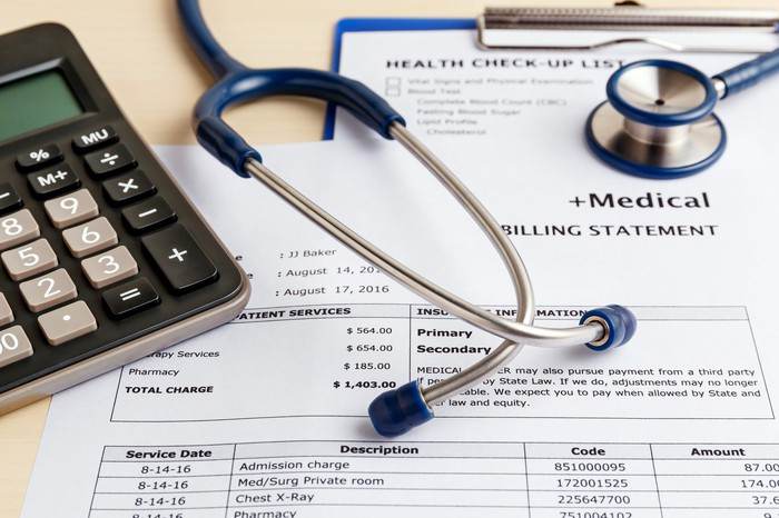 A stethoscope sits on top of a medical bill, next to a calculator.
