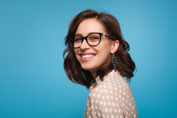 A smiling girl wearing glasses and looking at the camera.