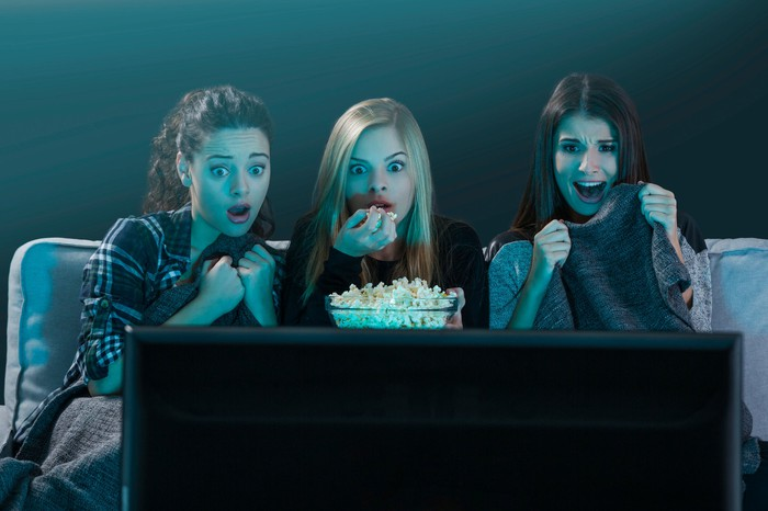 Three young women react to a scary movie on their TV.