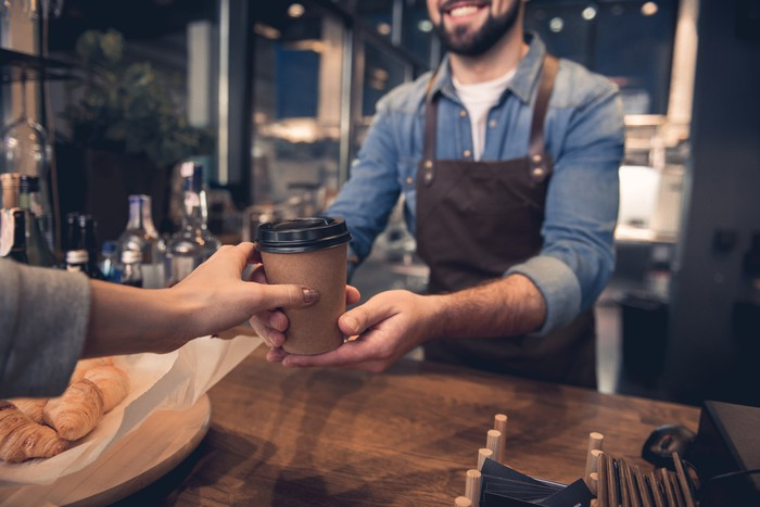 A barista handing a cup of coffee to a customer.
