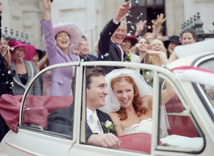 A bride and groom ride in the back of a car as people celebrate in the background