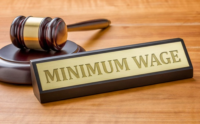 "A gavel with a nameplate that says ""MINIMUM WAGE"" in front of it."