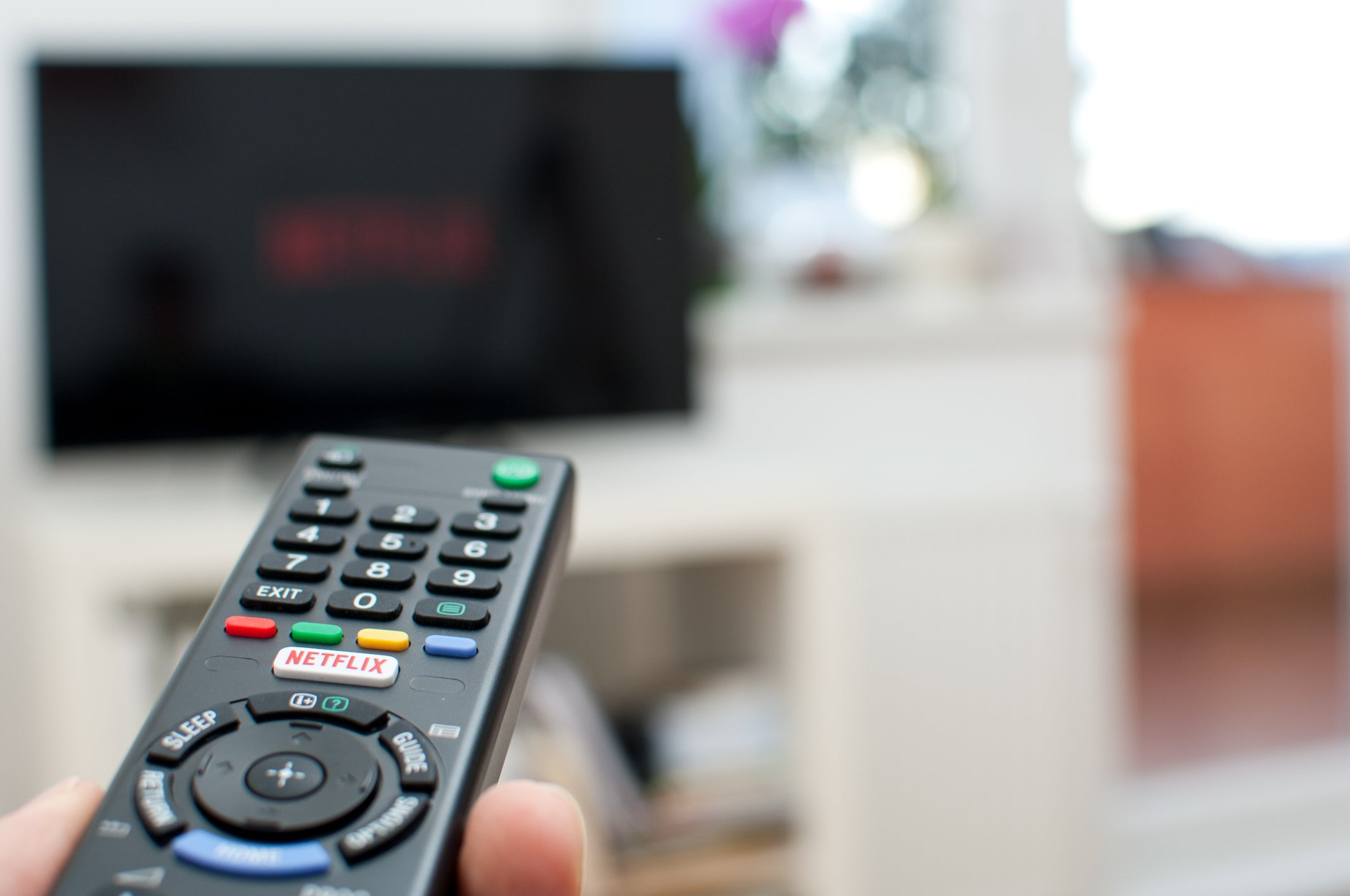 Remote control pointing toward television screen