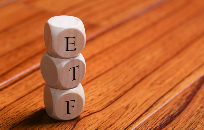 The letters E, T, and F on three dice on top of hardwood floor