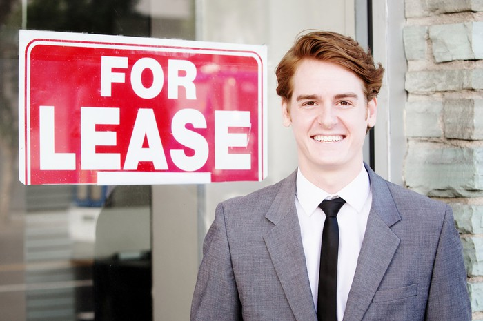 "Guy in front of a ""for lease"" sign"